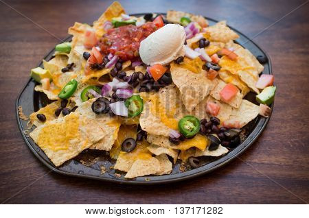 Vegetarian nachos loaded with toppings like jalapeno and black olives