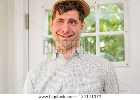 Young handsome curly haired man wearing newsboy hat making funny and idiotic smile