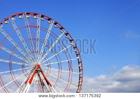 Ferris Wheel And Blue Sky With Clouds