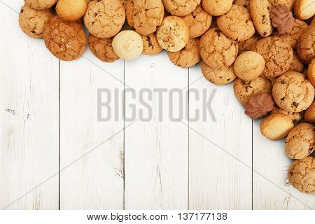 Cookies background. Sweet chocolate chips biscuits heap at white wood background with copy space. Oatmeal, chocolated drops and other sweets. Fattening dessert for tea on wooden table top view
