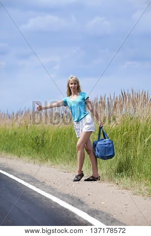 Hitchhiking girl on road on a sunny day