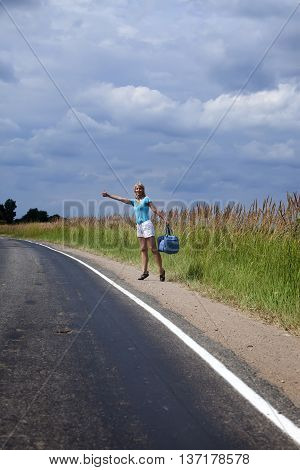 Hitchhiking girl votes on road in a sunny day