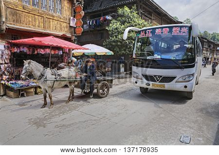 Zhaoxing Dong Village Guizhou Province China - April 8 2010: Chinese Public transport in the countryside of ethnic minorities shuttlebus and horse drawn vehicle.