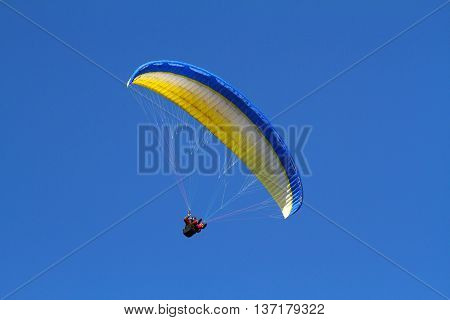 Yellow paraglider against the blue deep sky