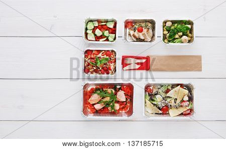 Healthy food delivery. Take away of natural organic low carb diet. Fitness nutrition in foil boxes, cutlery in brown paper package. Top view, flat lay with copy space at white wood