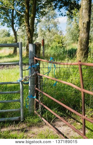 Closeup of a galvanized and a rusty gate closed off with a chain and padlock with blue ropes.