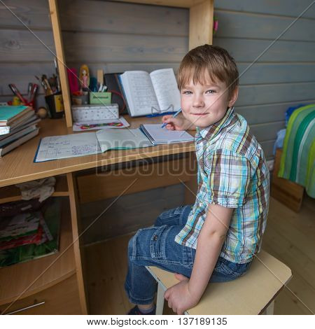 Little boy sitting at the table doing school homework.