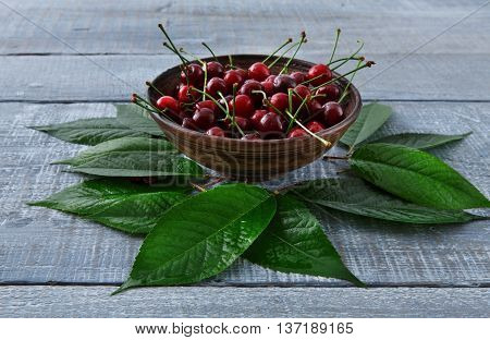 Sweet fresh cherries in bowl with green leaves background. Scattered fruits on blue rustic wood table. Healthy food.