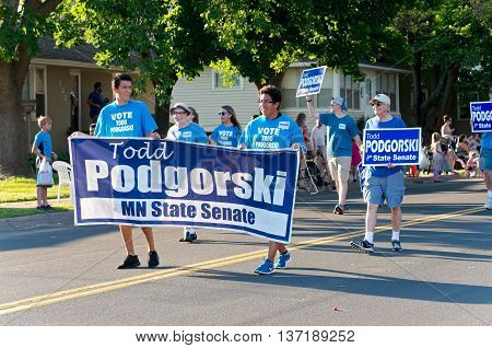 SOUTH ST. PAUL, MINNESOTA - JUNE 24, 2016: Supporters of Minnesota State Senate candidate Todd Podgorski hold election banner as they march at annual South Saint Paul Grande Parade on June 24.