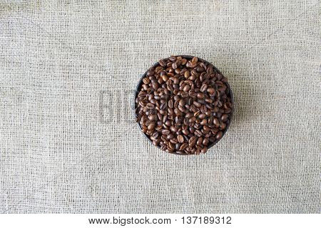 Burlap texture with coffee crop in a bowl background, plenty of robusta beans in plate. Sack cloth canvas with copy space. Heap of seeds at hessian textile