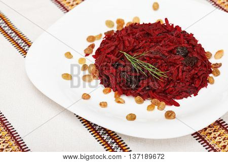 Grated beet salad with prunes and raisins served on a white plate and home tablecloth
