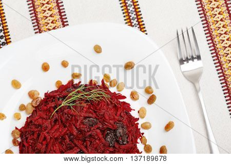 Grated beet salad with prunes and raisins served on a white plate and home tablecloth with fork. Top view. low aperture shot focus on beet and green