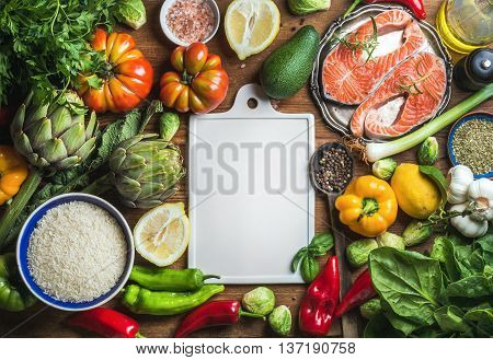 Two pieces of raw uncooked salmon fish in small metal plate, vegetables, rice, herbs, spices and olive oil on rustic wooden background with white ceramic board with copy space in center, top view, gorizontal copmosition
