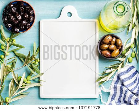 Two bowls with pickled green and black olives, olive tree sprigs and bottle of olive oil with white ceramic board in center over blue Turquoise background, copy space, top view