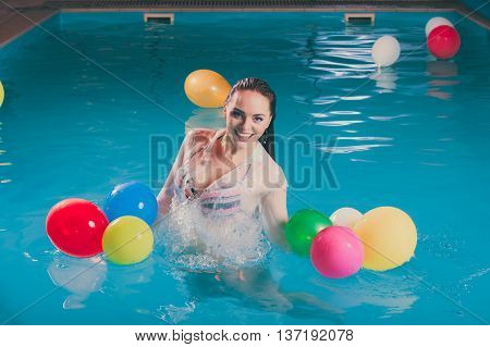Happy woman in swimming pool water having fun with balloons. Seductive young girl wearing wet white shirt relaxing.