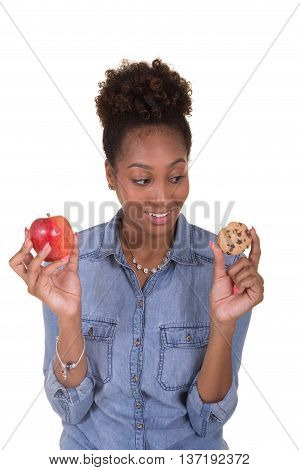 Concept shot of a young woman choosing between health food and junk food