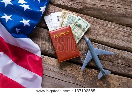 USA flag and a passport. Toy airplane near dollar bills. Visa for trip to America. Chance which costs a fortune.