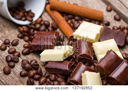 Roasted coffee beans and chocolate. White chocolate and cinnamon stick. Part of morning dessert. Snack for sweet tooth.