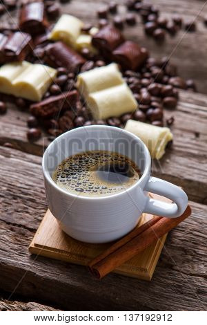 White cup with coffee. Cinnamon stick and chocolate. Traditional dessert after breakfast. Tastes like pure energy.