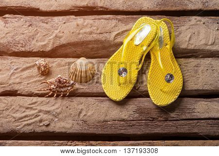 Flip flops and seashells. Yellow flip flops on sand. Travel and explore the world. Exciting adventures are waiting.