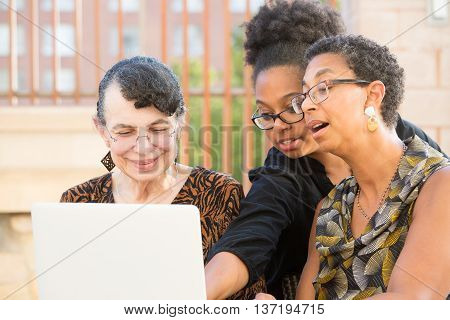 Closeup portrait multigenerational family looking at something exciting on laptop isolated outdoors background