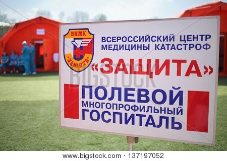 MOSCOW - APR 28, 2015: Signboard with the inscription: All-Russian Center of Disaster Medicine Protection, field multidisciplinary hospital in front of modular tents in the stadium