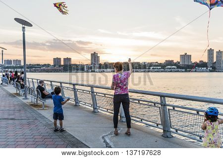 New York, USA - June 18, 2016: Woman and her kids fly kites on Pier 1 in Riverside Park in New York City during sunset
