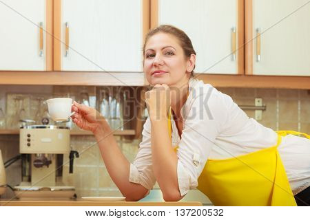 Pensive mature woman in apron holding cup of coffee in kitchen. Housewife female with hot energizing beverage. Caffeine energy.