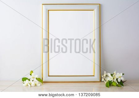 White frame mockup with apple blossom. Empty white frame mockup for design presentation. Portrait or poster white frame mockup romantic style.