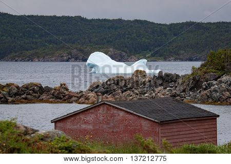 An iceberg floats in the ocean behind a red barn