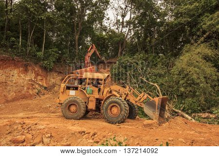 KOTA KINABALU, MALAYSIA - CIRCA JULY 2016: Deforestation. Blulldozer and excavator destroy tropical rainforest to make way for oil palm plantations.