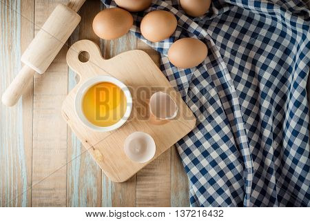 raw egg in a white bowl on wooden background