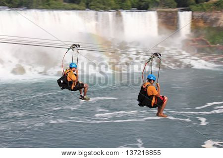 NIAGARA FALLS, ONTARIO. JULY 4 - 2016 There's a new attraction in Niagara Falls as we see two people heading toward the falls. For the brave at heart you can zipline along the escarpment of the Canadian side to a platform below and close to the Horseshoe