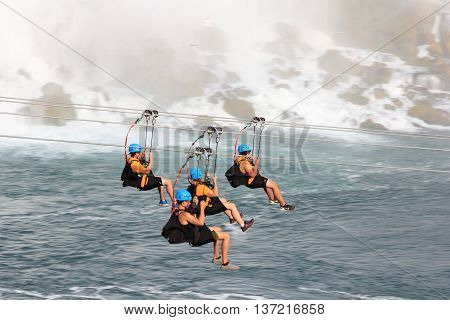 NIAGARA FALLS, ONTARIO. JULY 4 - 2016 There's a new attraction in Niagara Falls as we see four people passing in front of the Bridal Veil falls heading toward the Horseshoe falls. For the brave at heart you can zipline along the escarpment of the Canadian