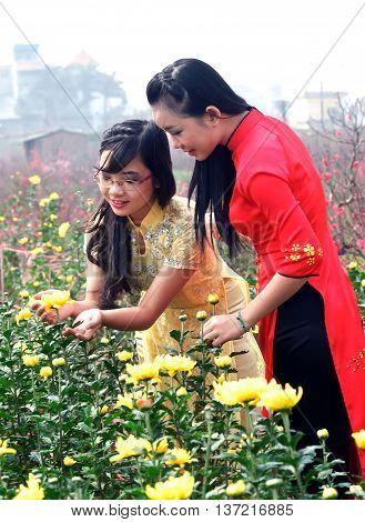 HA NOI, VIET NAM, February 12, 2016 two girls ha Noi, wearing traditional dress, walking gardens, Nhat Tan village, outside Hanoi, in the spring