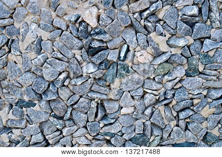 The wall built of fine granite gravel gray and black bonded with cement