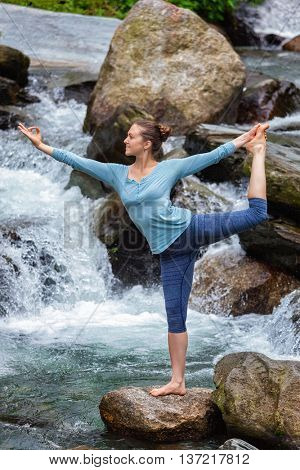 Yoga outdoors - woman doing yoga asana Natarajasana - Lord of the dance balance pose at waterfall in Himalayas