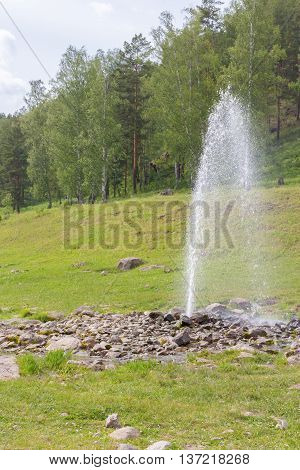 Natural fountain spouting from the ground on the banks of the river Ai. Ural Russia