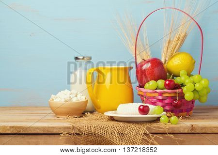 Fruits milk and cheese on wooden table. Jewish holiday Shavuot background