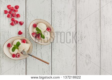 Vanilla ice cream with raspberries on wooden background
