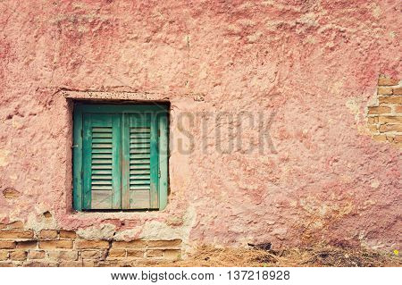 Old building detail with window and grunge red wall. Vintage background