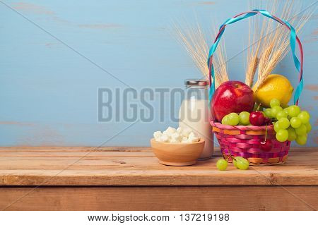 Jewish holiday Shavuot background with milk bottle and fruit basket on wooden table