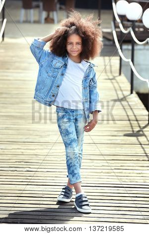 Afro American  little girl wearing denim clothes outdoors. Fashion kid concept
