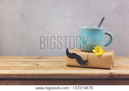 Coffee cup and gift box with paper mustache on wooden table. Father's day holiday concept
