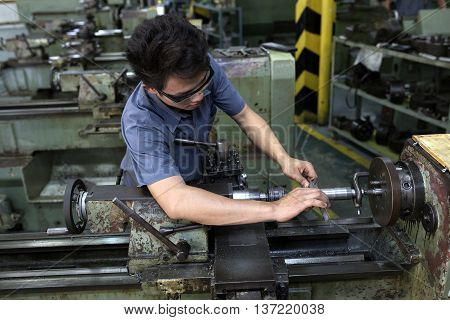 The man check technician worker at metal machining milling lathe in tool workshop