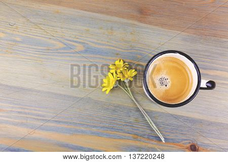 Vintage enamel coffee cup and daisy flowers on wooden table. View from above