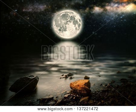 month on a background star sky reflected in the sea. Elements of this image furnished by NASA