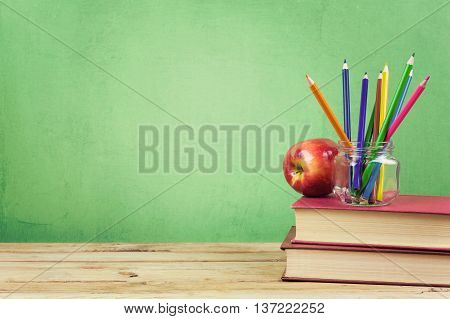 Back to school background with books color pencils and apple over green wallpaper