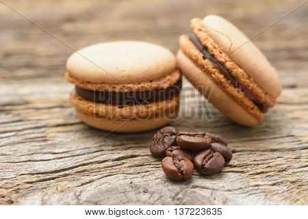 French cocoa macaroons with coffee beans on wooden table