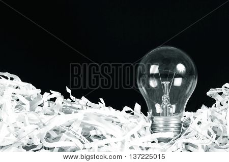 the Light bulb place on shredded recycled paper on black background idea innovation concept